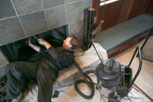 man vacuuming inside of fireplace cleaning it