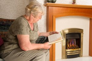 Woman Reading by the gas Fireplace